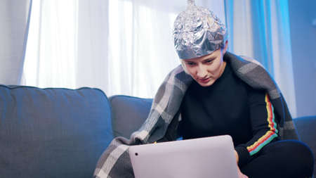 young woman with aluminum hat reacting badly on the conspiracy theory post about 5g microwaves and connection. High quality photo