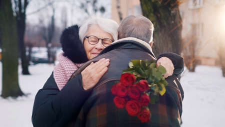 Valentines day. Happy elderly man giving bouquet of red roses to his date in winter. Hugging un the park. High quality photo