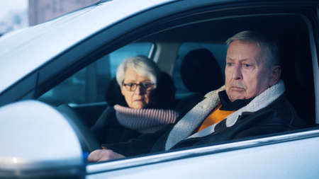 Retired couple testing new car. Winter vacation at old age. High quality photo