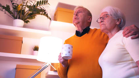 Elderly couple hugging and speaking on the phone while watching tv. . High quality photo
