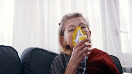older woman using a respiratory mask inhaling medicine to clear out her throat and sinuses. High quality photo