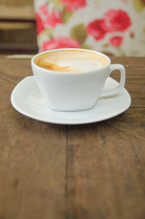 A cup of coffee on wooden table photo