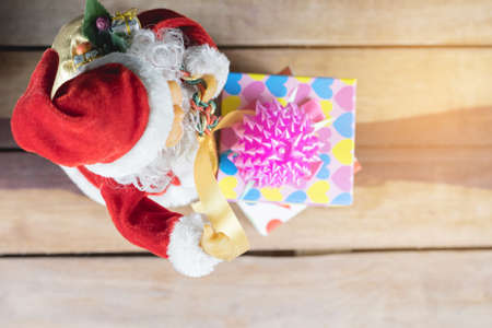 Top view Santa toy and gift boxes on wooden table.