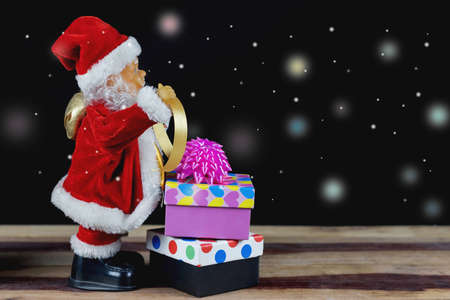 Santa toy and gift boxes on wooden table.