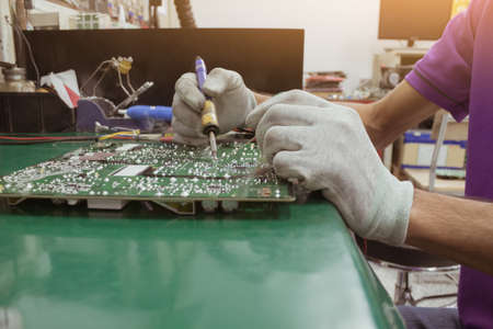 The repair man using soldering iron on circuit of PCB board on table ESD mat. Reklamní fotografie