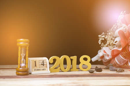 Bouquets of dried flowers, hourglass, wooden plate with letters, February 14, 2018 on wooden table.