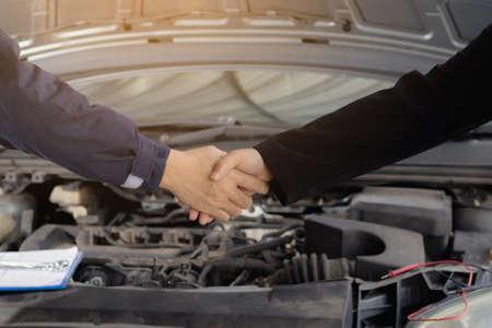 Repair man and woman handshake front of car. Reklamní fotografie