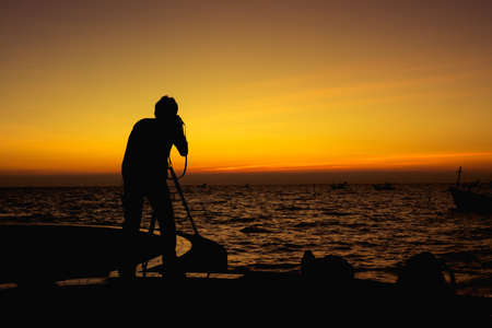 Silhouette of photography man on the beach and sky with beautiful sunset. Reklamní fotografie