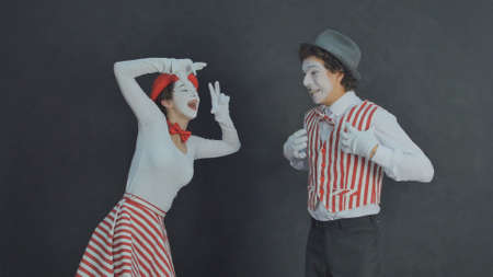 Young funny mimes scene show pictures of each other