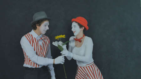 Young mimes show scene with flower