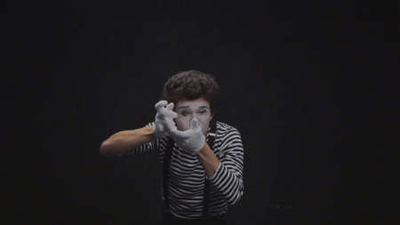 Mime boy photographed on black background
