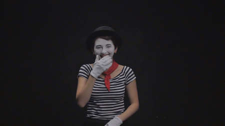 Mime girl laughing on black background Stock Photo
