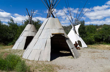 first nations: Three tipi and a metal sculpture depicting a typical summer Okanagan village. Editorial