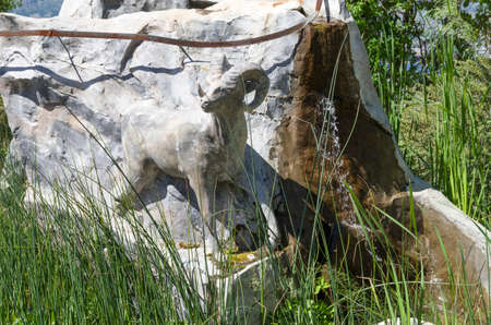 first nations: Stone staue depicting a big horn sheep in natural surroundings and seeking out water. Editorial