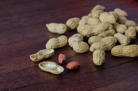 Peanuts in shells on a dark wooden kitchen board Stock Photo