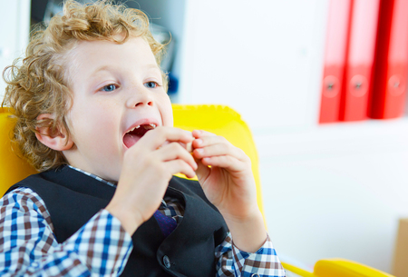 Small Caucasian boy opened his mouth holding a sandwich with sausage. he looks at the monitor while sitting in the office 写真素材