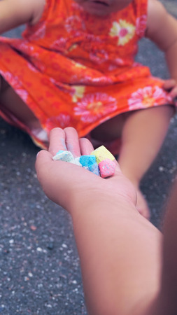 Mom gives the girl crayons for drawing on the asphalt Stock Photo