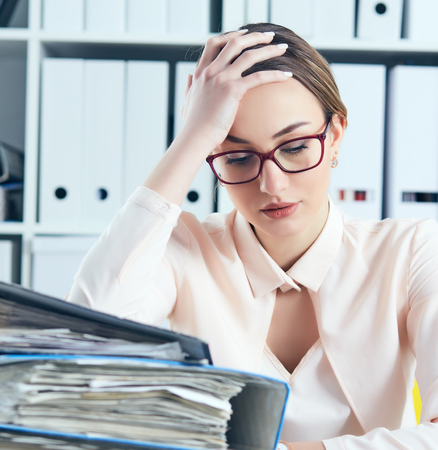 Tired and exhausted woman in spectacles looks down near the mountain of documents propping up her head with her hands.