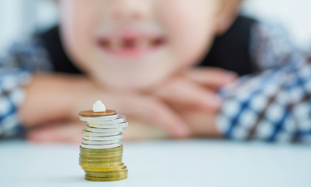 Smiling young boy with missing front tooth. Pile of coins with a baby tooth on top. 免版税图像
