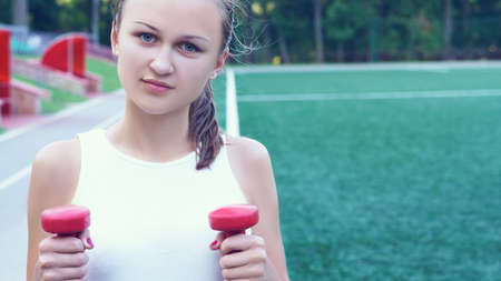 Beautiful sporty red-haired girl goes in for sports in the street with a metal dumbbell at the stadium. Zdjęcie Seryjne