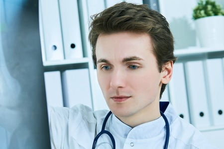 Close up portrait of young male doctor holding x-ray or roentgen image. Stock Photo