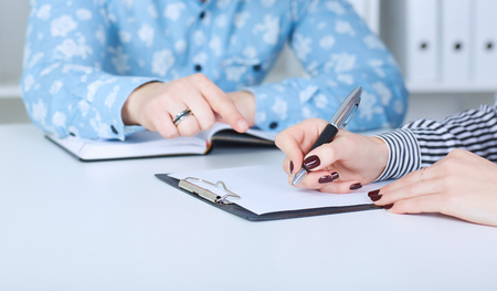 The employer forces the employee to write a letter of resignation. Just hands over the table. Stock Photo