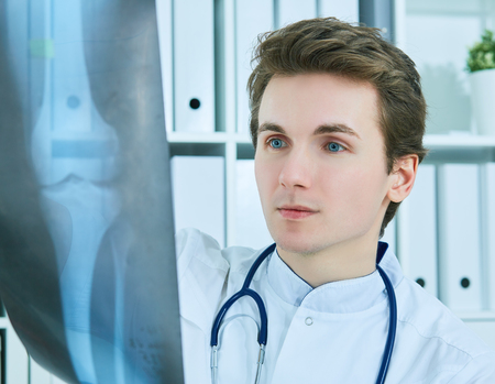 Close up portrait of young male doctor holding x-ray or roentgen image. Stok Fotoğraf