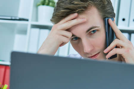 Close-up portrait of white collar talking to customer on mobile phone in office at workplace by laptop. 스톡 콘텐츠