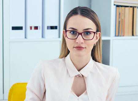 Portrait of young serious businesswoman looking at the camera while using laptop in office.