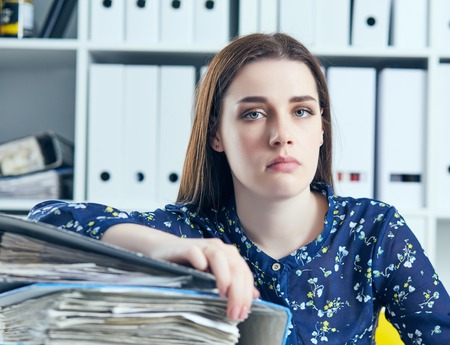 Young tired and exhausted woman looks at the camera leaning against mountain of documents propping up her head with her hands.