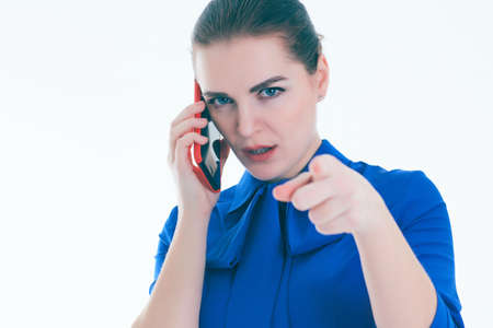 Serious woman talking on mobile phone and points a finger at you. Isolated on white. 스톡 콘텐츠