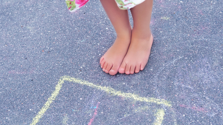 Closeup of little boys legs and hopscotch drawn on asphalt. Child playing hopscotch game on playground outdoors. Stock Photo