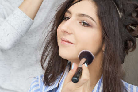 Master inflicts brush powder on the face of the girl, completes the day make-up in a beauty salon. Imagens - 134803138