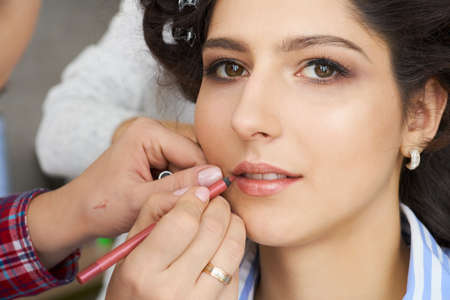 The make-up artist doing a makeup for bride.