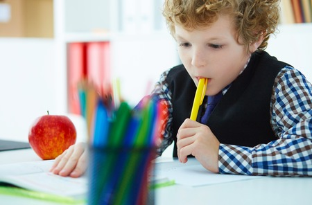 Curly Caucasian boy thought about the task and took a pen in his mouth during the lesson at school. Education, childhood, people, homework and school concept.