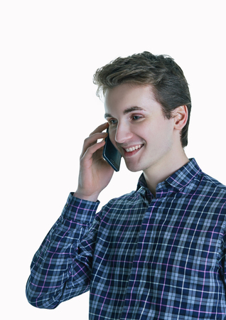 Cheerful young man speaking on the phone on white background. Banque d'images - 112749028