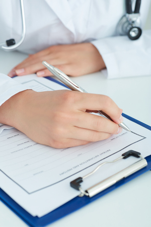 Female medicine doctors hands filling patient medical form. Physician working with paper in hospital office room.