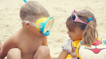Portrait of the happy children with swimming mask on head playing onthe sea beach.