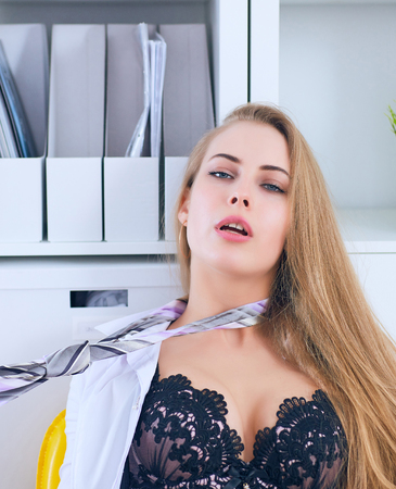 Sexy secretary undresses in office and pull the tie on her neck. Flirt and desire, office provocation. Stok Fotoğraf
