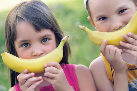 Close up faces of a beautiful young caucasian girl and boy with banana smile Banco de Imagens