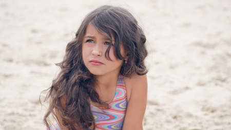 Close-up portrait of a pretty little Hispanic girl with waving in the wind long hair sitting on the beach. Standard-Bild