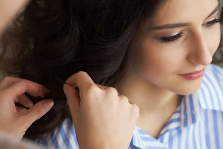 Closeup view of the hand and comb of a hairstylist combing a new hairstyle on a customer head in hair salon. Фото со стока