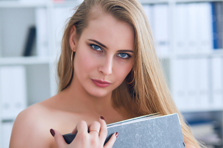 Beautiful young secretary hides her nakedness for a folder on an office background. Harassment concept. Stock Photo - 112763759