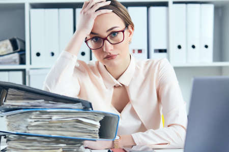 Young tired and exhausted woman in spectacles looks at the camera leaning against mountain of documents propping up her head with her hands. Фото со стока