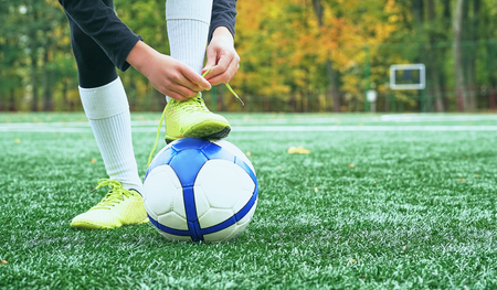 Boy football soccer tying the laces on the boots on grassy football stadium. Stockfoto