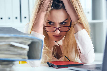 Tired and exhausted woman in spectacles looks at the mountain of documents propping up her head with her hands.
