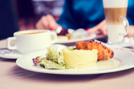 Chicken Kiev on croutons with mashed potatoes and salad, on the table in cafe.