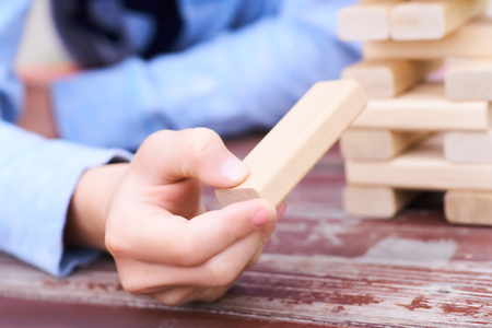Close up kids hand playing wood blocks tower game for practicing physical and mental skill.