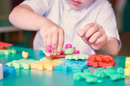 Middle section of little boy playing with colorful plastic bricks at the table. Kids having fun and building out of bright constructor bricks. Early learning. Developing toys