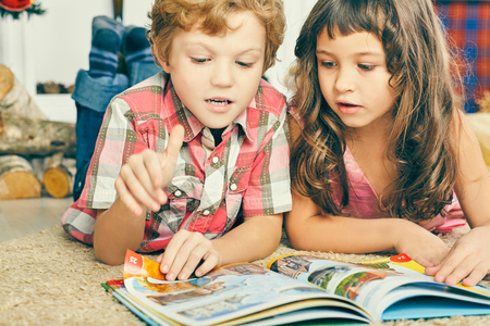 Little boy and girl lying on the floor and reading breathtaking book. Stok Fotoğraf - 112765747
